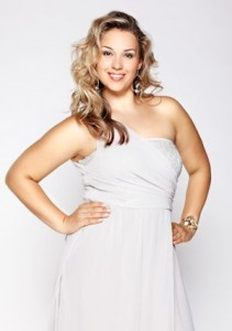 portrait of beautiful plus size curly young blond woman posing on gray
