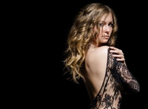 young gorgeous lady posing in lace dress over black. space for copy